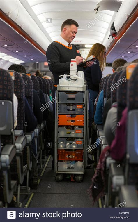 Cabin crew / air steward serves drinks and snacks to