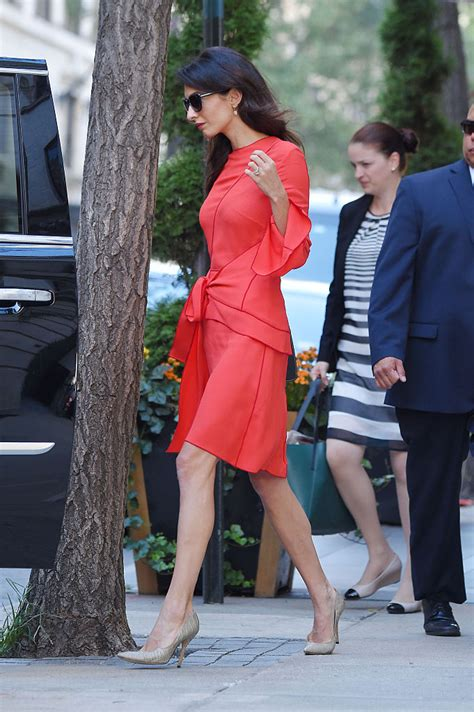 Amal Clooney shows off long legs in red wrap dress