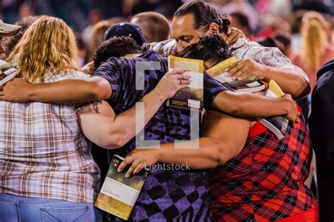Stock Photo - A group of people praying in a circle with
